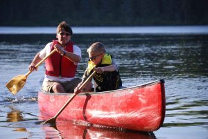 father_and_son_paddle_a_canoe_on_river